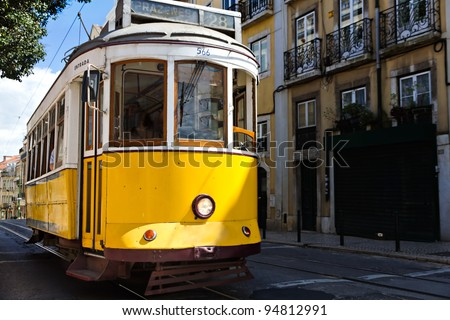 historic classic yellow tram of Lisbon built partially of wood navigating, narrow, winding streets, Portugal - stock photo