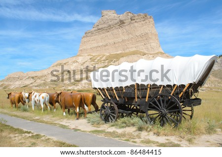historic covered wagon and oxen next to Scotts Bluff National Monument - stock photo
