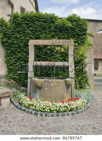 historic draw well in Mittelbergheim, a village of a region in France named Alsace - stock photo