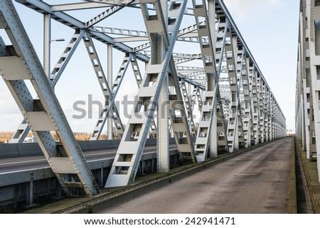 Historic gray painted Dutch riveted truss bridge against a blue sky. - stock photo