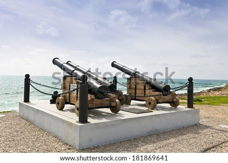 Historic guns at the harbor in Paphos facing the sea. - stock photo