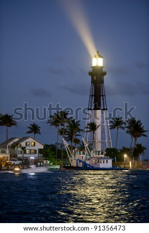 historic hillsboro inlet lighthouse in florida shining in evening beside ocean inlet and dredging rigs, actual beam - stock photo