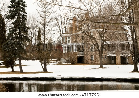 historic home in winter with river in front