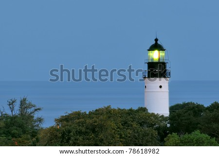 historic key west, florida, lighthouse beaming on clear night with ocean in background
