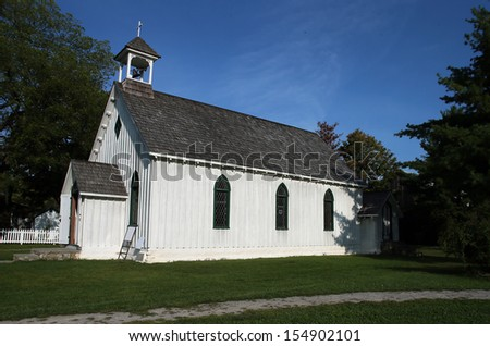 Historic Little White Church with cross and bell tower - stock photo
