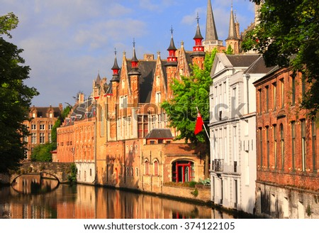 Historic medieval buildings along a canal in Bruges, Belgium - stock photo