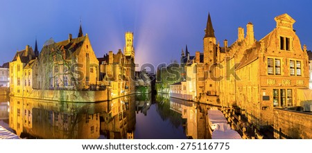 Historic medieval buildings along a canal in Bruges, Belgium at dusk. - stock photo