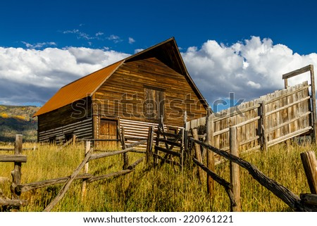 Historic Moore Barn in Steamboat Springs Colorado with mountain slopes filled with fall color on warm autumn evening - stock photo