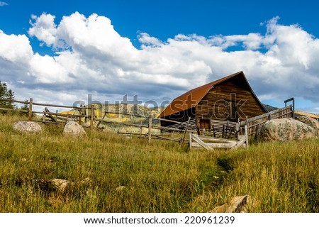 Historic Moore Barn in Steamboat Springs Colorado with mountain slopes filled with fall color on warm autumn afternoon - stock photo
