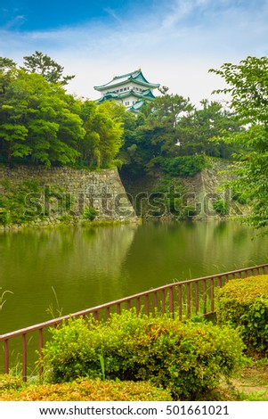 Historic Nagoya Castle stronghold above its rampart walls across the water moat in center Nagoya, Japan