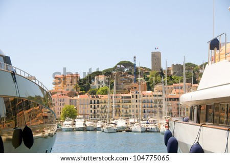 historic Old City between two yachts Cannes French Riviera Cote d'Azur Cannes France - stock photo