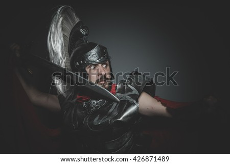 Historic, Praetorian Roman legionary and red cloak, armor and sword in war attitude - stock photo