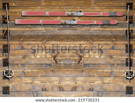 Historic red coated ski  with poles fixed on a wooden board - stock photo