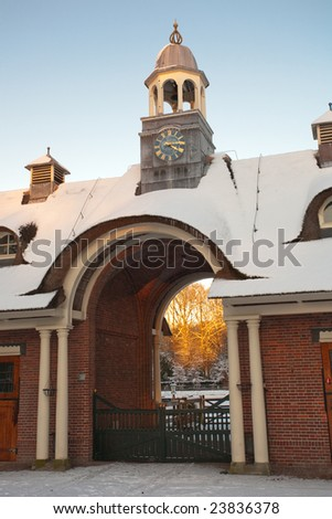 Historic stable with gate covered with snow - stock photo