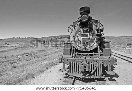 Historic Steam Engine crossing Rocky Mountains between Colorado and and New Mexico.  Converted to black and white from color original - stock photo