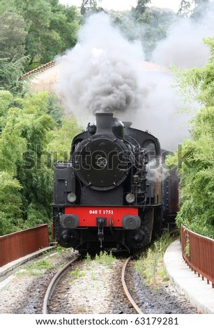 Historic steam engine with heavy dark grey smoke. Southern France near Nimes - stock photo