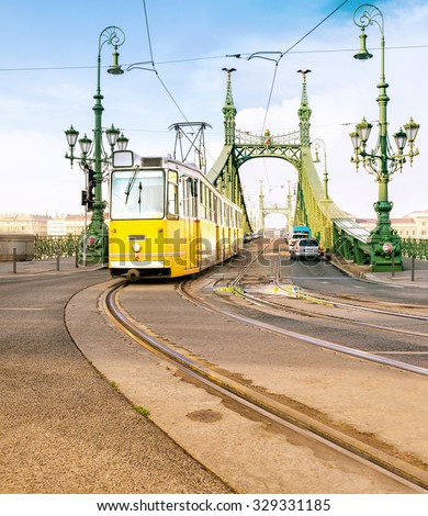Historic tram on Freedom Bridge in Budapest, Hungary, on a bright day. This image is toned. - stock photo