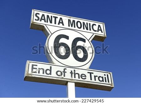 Historic U.S. Route 66 signpost in Santa Monica California, a road stretching from Chicago to Los Angeles which became synonymous with automobiles and driving itself. - stock photo