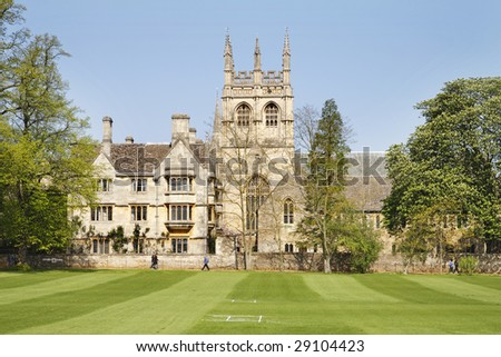 Historic University Building in Oxford City, England with cricket field in front and Church in the background - stock photo