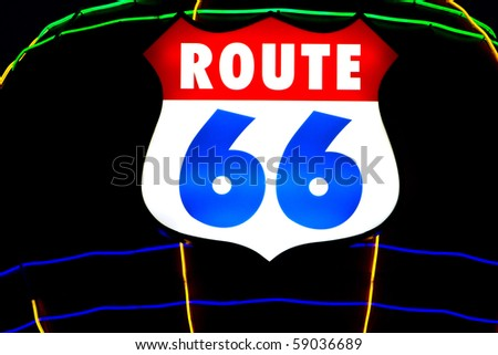 Historic US Route 66 sign with neon lights at night