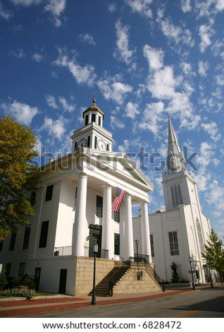 Historic White Stone Courthouse and Church against a Cloud Filled Sky - stock photo