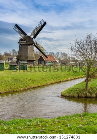 Historic windmill next to canal in Holland