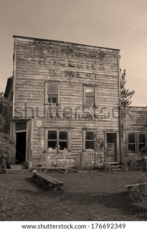 Historic wooden building, the old hardware store of mining town McCarthy, Alaska, USA. Sepia filter, vintage style. - stock photo