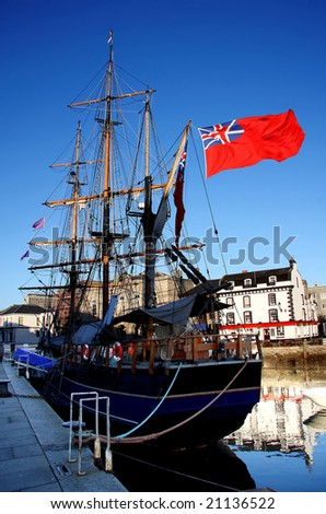 historical battleship with flag of England in the harbor, Plymouth, UK - stock photo