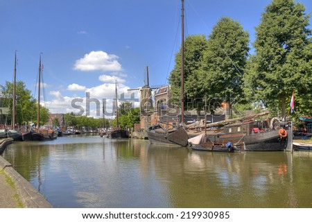 Historical boats and windmill on a canal in the Dutch town Gouda, Holland - stock photo