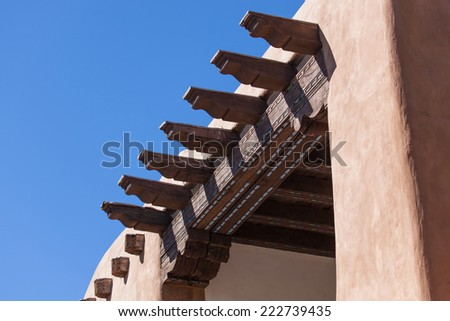 Historical building with wooden support beams in traditional southwestern style with a blue sky background. - stock photo