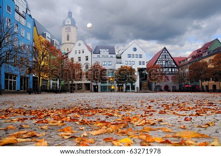 Historical buildings facing the market square, still empty in the foggy morning. There is a flying balloon catching a glimpse of sunshine. City of Jena, Thuringia, Germany - stock photo