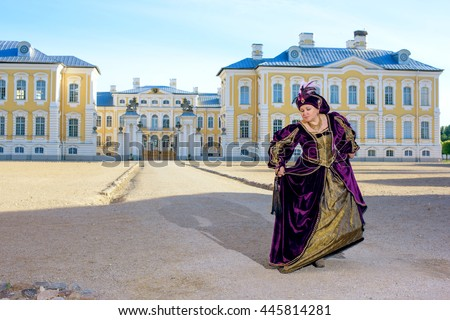 Historical cosplay. Beautiful woman in the similitude of Isabella d'Este Mantua, marquess of Italian ancient dress near palace - stock photo