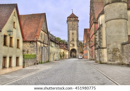 Historical houses and a city wall tower in the old city of Rothenburg ob der Tauber, Germany - stock photo