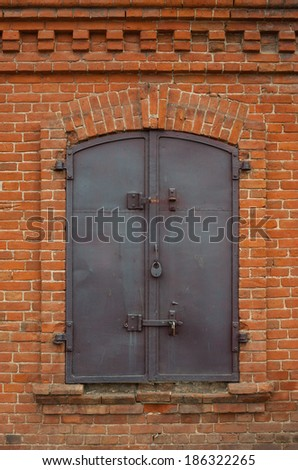 Historical old closed metal window shutter in brick wall - stock photo