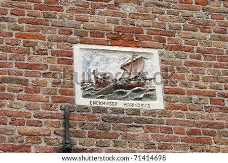 Historical plaque on a brick wall in the old  fishing town  of Enkhuizen, Netherlands commemorating the fishermen - stock photo