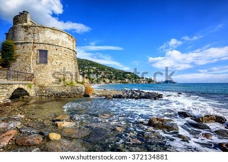 Historical Saracen tower on mediterranean beach in Alassio, popular resort town on italian Riviera, Liguria, Italy - stock photo