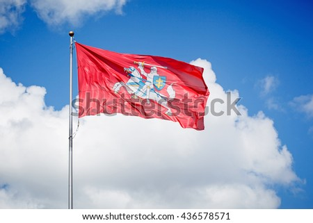 Historical state flag of Lithuania waving over blue cloudy sky