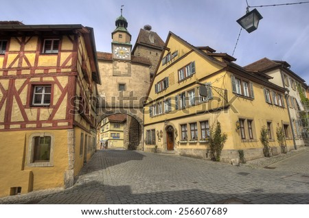 Historical street with ancient houses and hotels and an old gate and clock tower in Rothenburg ob der Tauber, Germany - stock photo