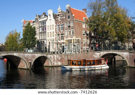 Historical touring boat in an Amsterdam canal - stock photo