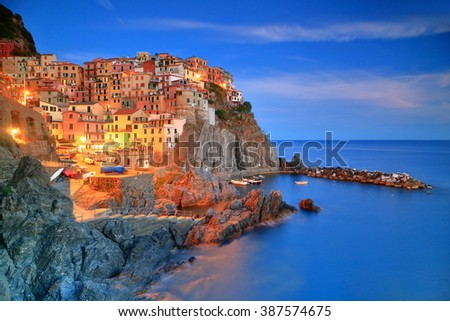 Historical village and harbor of Manarola illuminated by night, Cinque Terre, Italy