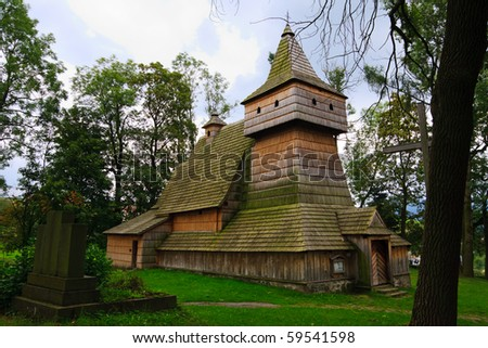 Historical wooden church in polish heritage park. Blue sky and clouds in a background. - stock photo
