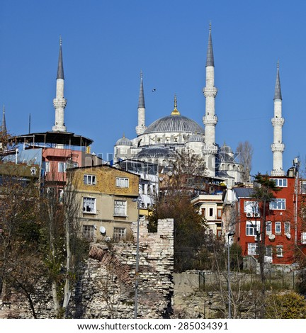 History meets nowadays. Ancient ruins of Theodora Byzantine Wall in Istanbul small colorful houses and minarets of Ottoman Blue Mosque on background sunlight blue sky - stock photo