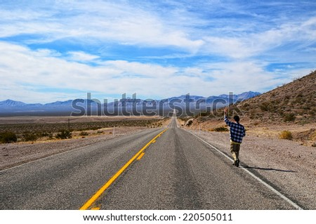 Hitchhiker on a road - stock photo