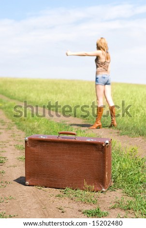 hitchhiker with an old leathern suitcase - stock photo