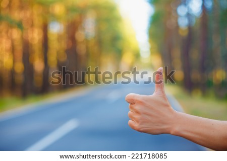 Hitchhikers sign thumb up at road background on summer day closeup  - stock photo