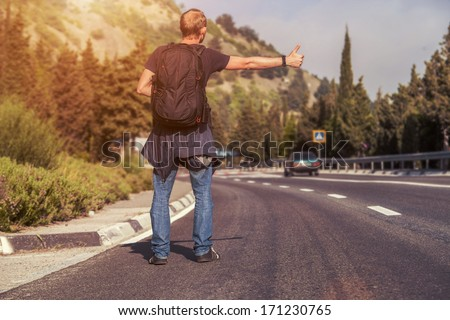 Hitchhiking traveler try to stop car on the mountain road - stock photo