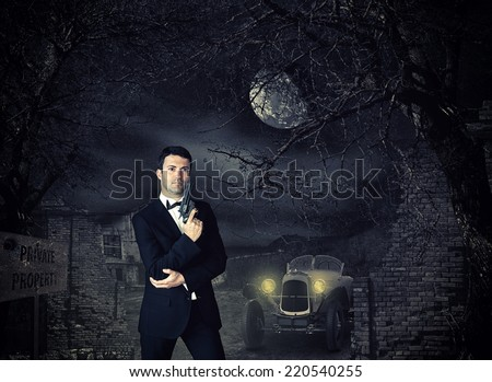 Hitman  in tux holding a gun - stock photo