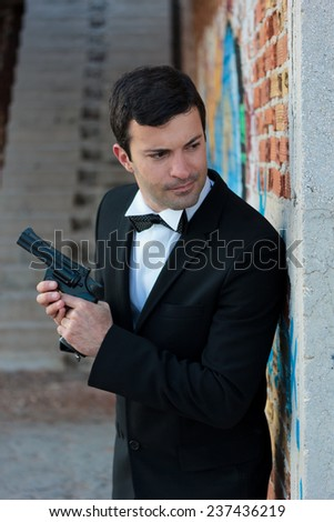 Hitman in tuxedo holding a gun - stock photo