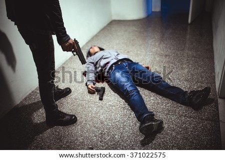 Hitman with dead victim - stock photo