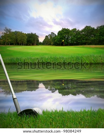 hitting golf ball over water hazard from fairway onto green - stock photo